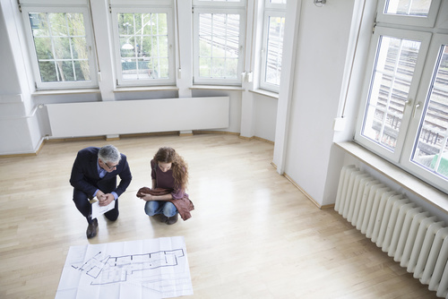 Real estate agent showing construction plan to client in empty a